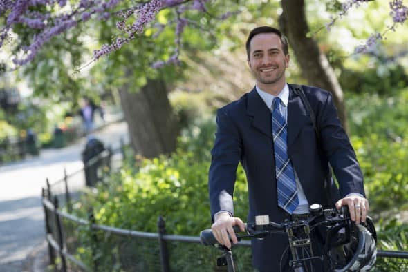 A man in a business suit astride a bicycle with helmet in hand.