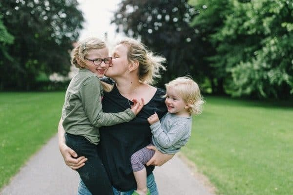 Mother Holding Kissing Children