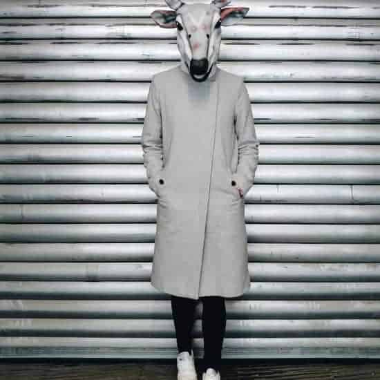 hipster man with coat and reindeer mask