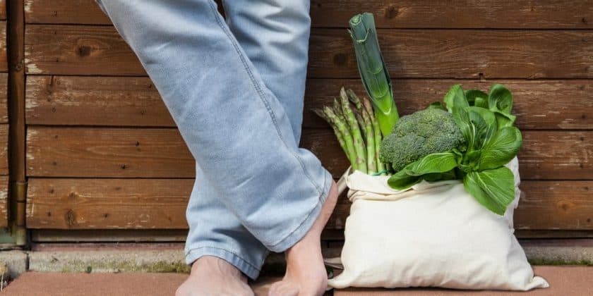 Jute bag with vegetables next to man in jeans and bare feet