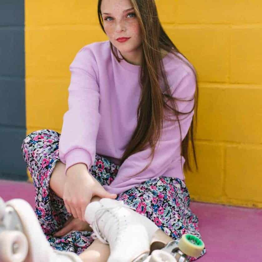 Teenage girl with roller skates sitting near yellow wall