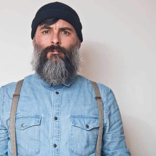 Portrait of bearded man in denim shirt and suspenders