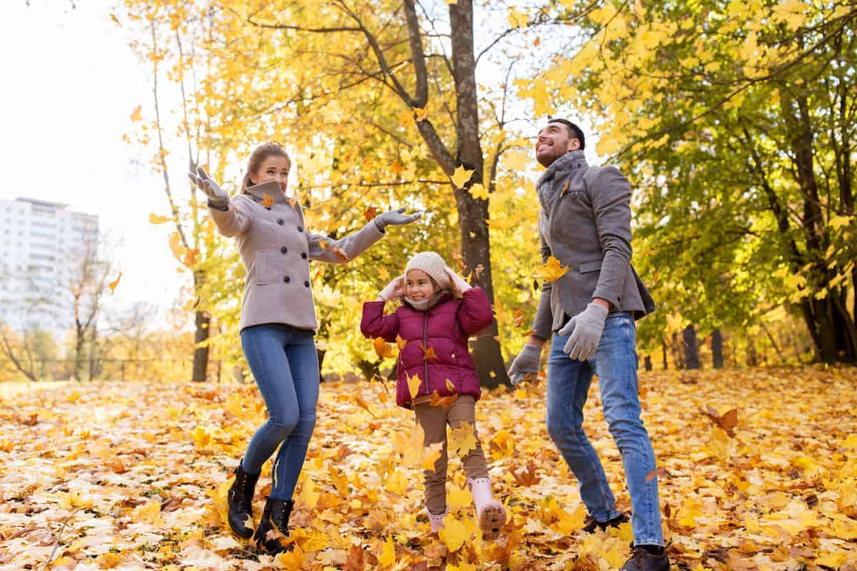 happy hispanic family, mother, father and little daughter playing with autumn leaves at park