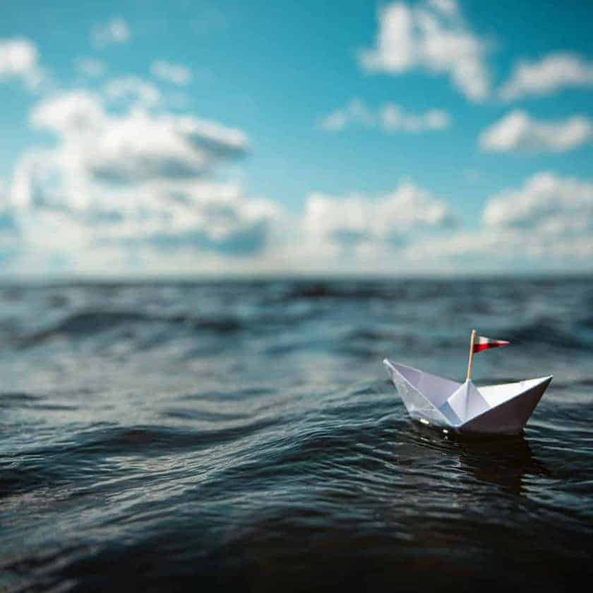 Paper boat on the high seas, clouds on the horizon