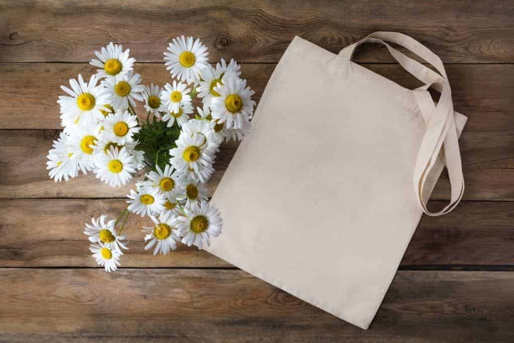 Tote bag with daisy bouquet on wooden table