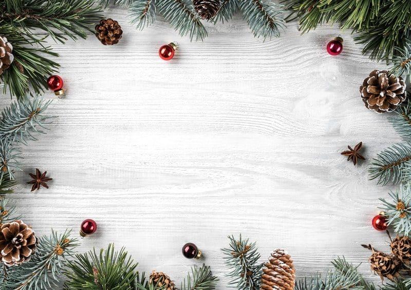Vánoční větve a baňky na světlé dřevěné desce