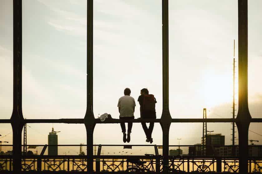 Men sitting on bridge at sunset
