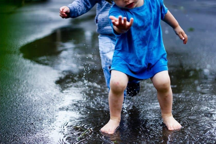 Children playing in puddle rain