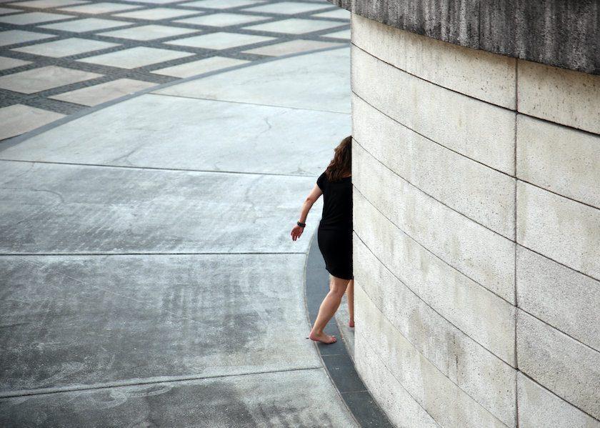 Woman walking behind wall