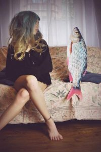Attractive woman sitting on couch next to a fish