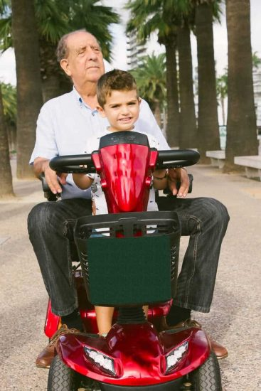 Older man with boy riding on electric vehicle for disabled on promenade