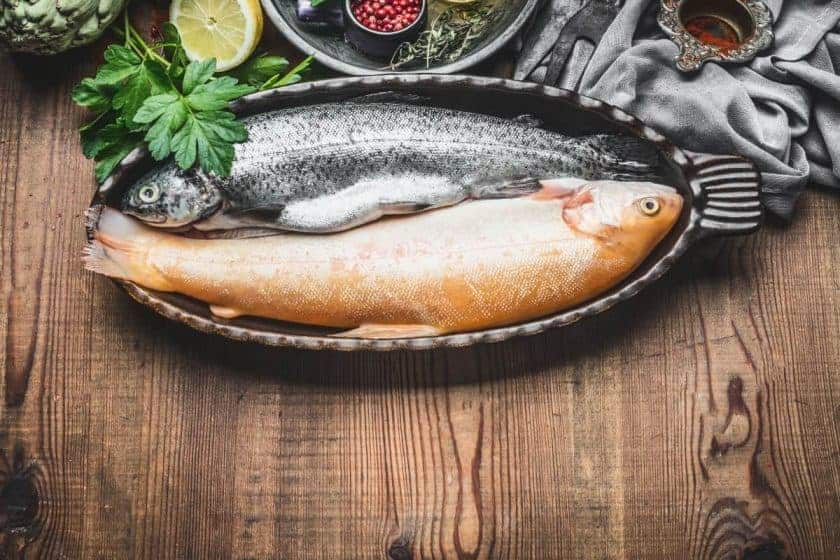 2 fresh trouts in bowl on wooden table