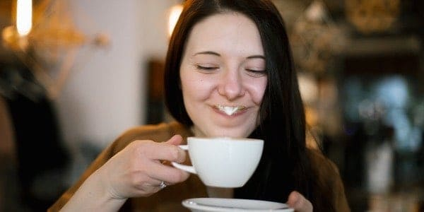 woman smiling with milk mustache coffee
