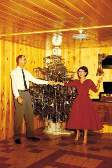 Vintage photo of man and woman dancing in front of Christmas tree