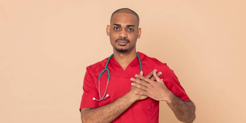 african doctor red gown hands to heart