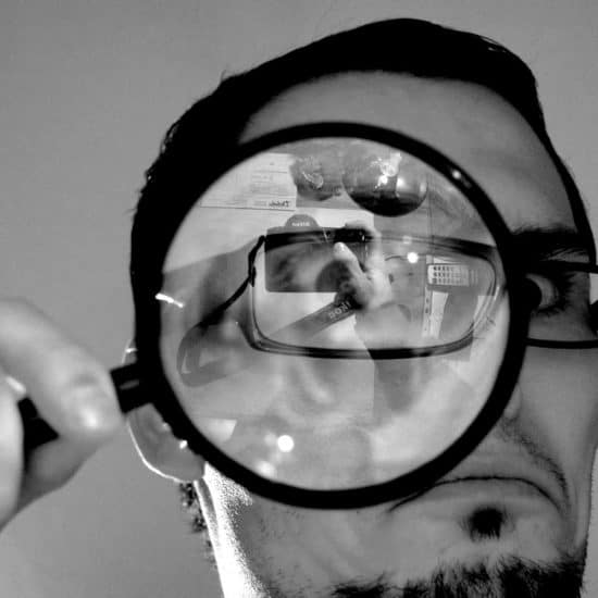 Close up of man holding a magnifying glass