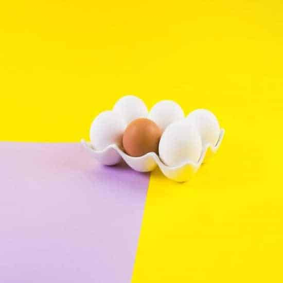 White and one brown egg on yellow and purple