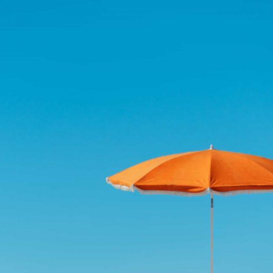 orange parasol in front of a blue sky