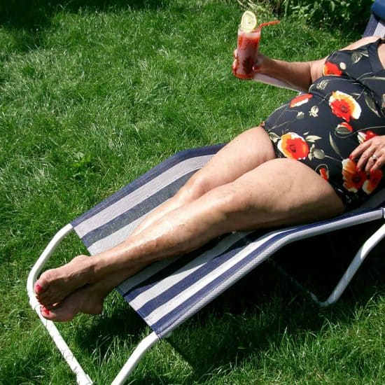 senior lady with swimsuit in a deck chair with a drink