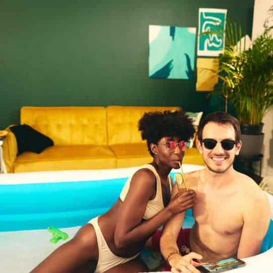 multiethnic couple resting in inflatable pool with some drinks