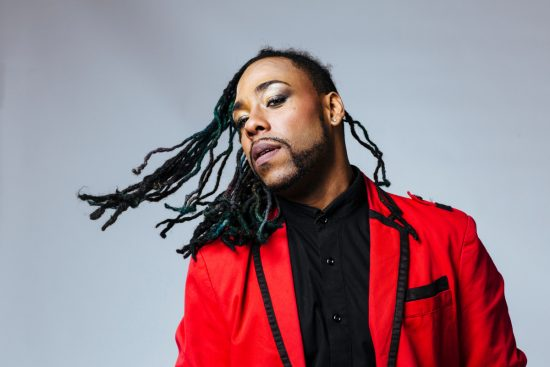 Studio portrait of a man wearing a red jacket suit and dreadlocks > Exciting Photography Trends 2021