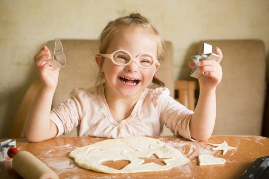 happy girl with Down syndrome bakes cookies > Exciting Photography Trends 2021
