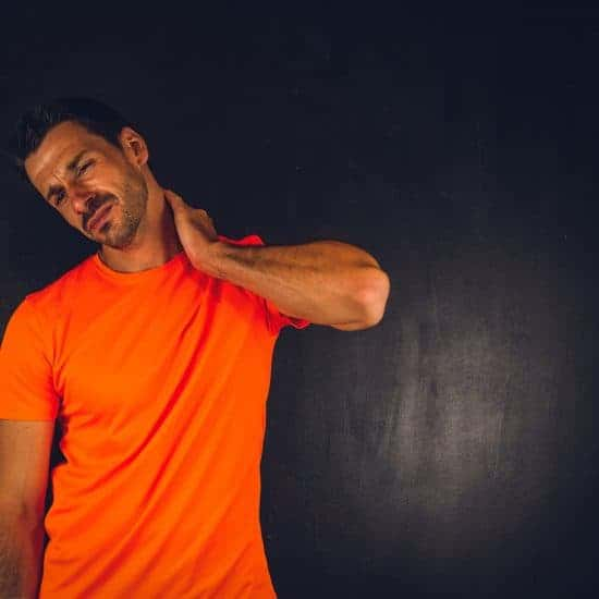 Man in orange shirt with sore neck