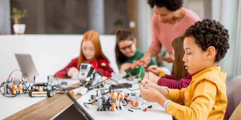 kids with african american female science teacher with laptop in robotics class